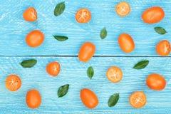 Cumquat或金桔与叶子在蓝色木背景 顶视图 平的位置样式 免版税库存图片