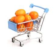 Cumquat或金桔与叶子在购物车在白色背景 库存图片