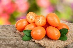 Cumquat lub kumquat z liściem na starym drewnianym stole z rozmytym ogrodowym tłem Zdjęcie Royalty Free