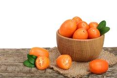 Cumquat lub kumquat z liściem w drewnianym pucharze na starym drewnianym stole z białym tłem Zdjęcie Stock