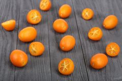 Cumquat lub kumquat z połówką na bllack drewnianym tle Fotografia Stock