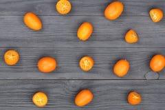 Cumquat lub kumquat z połówką na bllack drewnianym tle Odgórny widok Mieszkanie nieatutowy wzór Zdjęcia Stock
