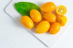 Cumquat oder japanische Orange mit gr?nem Blatt auf wei?em h?lzernem Hintergrund stockbild