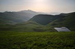 Cumulez deux emplois complètement près du lac montagneux image libre de droits