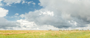 Cumulus on azure sky above harvested grain field Royalty Free Stock Photo