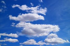 Cumulus blancs purs flottant sur le ciel bleu vif photographie stock libre de droits