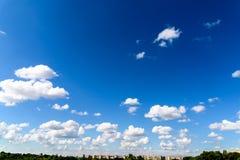 Cumulus blancs sur le ciel bleu au-dessus des bâtiments de ville de Bucarest Image libre de droits