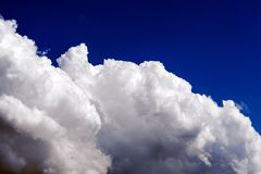 Cumulus blancs sur un fond profond de ciel bleu images libres de droits
