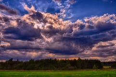 Cumulus chmury przy lata światła dziennego above zieloną łąką typową dla lata lub wiosny sezonu Fotografia Stock