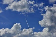Cumulus chmury w niebieskim niebie i samolotowym śladzie zdjęcie royalty free
