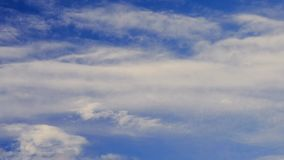 Cumulus and cirrus clouds move on background of blue sky. Time lapse of scenic cloudscape with white cumulus and cirrus clouds moving horizontally from left to stock video footage