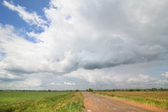 Cumulus clouds above the road in the steppe. Royalty Free Stock Image