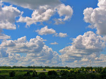 Cumulus clouds cascade on a bright blue sky Stock Photo