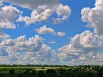 Cumulus clouds cascade on a bright blue sky Stock Photo