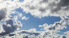 Cumulus Clouds And Grey Storm Clouds Gathering On Blue Sky. White Cumulus Clouds And Grey Storm Clouds Gathering On Blue Sky stock images