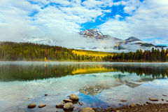The cumulus clouds. Indian Summer in Canada. Patricia Lake among the pines. The water reflects the peak of the Pyramid Mountain and the lush cumulus clouds. The royalty free stock photo