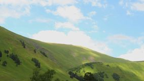Cumulus clouds moving across blue sky, green hills, time-lapse. Stock footage stock video footage