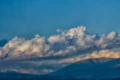 Cumulus clouds moving over mountains Royalty Free Stock Image