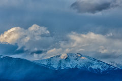 Cumulus clouds moving over mountains Stock Photography