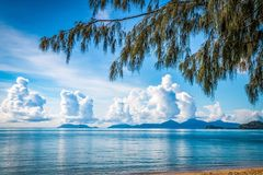 Cumulus clouds over Cairns. Cumulus clouds gather at the horizon from a tropical beach Stock Image