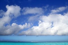 Cumulus clouds over caribbean turquoise sea Stock Photos