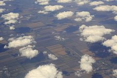 Cumulus clouds over the fields from airplane view. Cumulus clouds over the fields from the airplane view royalty free stock photo
