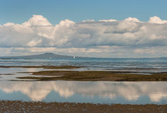 Cumulus clouds reflecting in tide pool Stock Photography