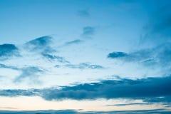 Cumulus du coucher du soleil avec le fond brouillé de ciel bleu de coucher du soleil defocusing photographie stock libre de droits