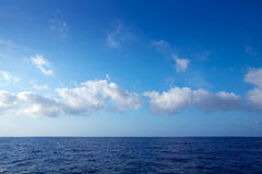Cumulus en ciel bleu au-dessus d'horizon de l'eau photographie stock libre de droits