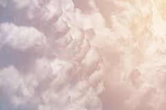 Cumulus fluffy clouds illuminated by orange sunlight as background. Abstract, toned stock photography