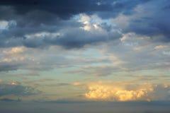 Cumulus lumineux du soleil et nuages foncés le soir SK images stock