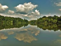 Cumulus Mirror Reflection Over Lake. Cumulus clouds reflecting over a mirror lake. Marvelous dense green foliage Royalty Free Stock Photography