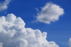 Cumulus pelucheux blancs flottant sur le ciel bleu vibrant image libre de droits