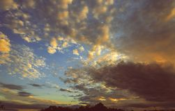 Cumulus sunset clouds with sun setting down Dramatic Sunset sky Toned Image. Dramatic Sunset sky clouds with sun setting down Toned Image Royalty Free Stock Image