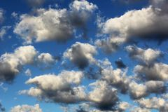 Cumulus white puffy fluffy clouds against deep blue sky. Abstract background landscape Stock Image