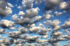 Cumulus white puffy fluffy clouds against deep blue sky. Landscape background Royalty Free Stock Photo