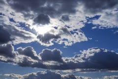 Cumuluswolken op blauwe die hemelachtergrond met zon wordt benadrukt royalty-vrije stock foto's