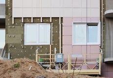 cuna amarilla suspendida construcción sin los trabajadores en un edificio alto, una arena, ventanas y una estructura nuevamente c Imagen de archivo