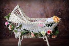 Cuna de mimbre florecida del bebé Fotos de archivo