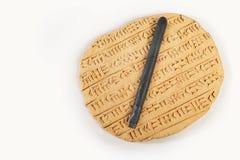Cuneiforme do estilo do império de Akkad escrito na argila marrom com ferramenta da escrita foto de stock royalty free