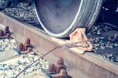 Cuneo della ruota sotto la ruota del treno sulle rotaie fotografie stock libere da diritti