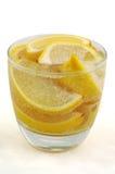 Cunhas de limão na água mineral de vidro Imagem de Stock
