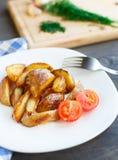 Cunhas fritadas da batata com tomate de cereja Fotografia de Stock Royalty Free