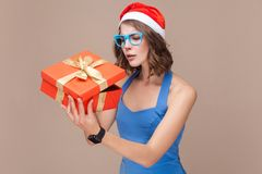 Cunning businesswoman looking at gift box and want too open. Brown background. Studio shot Stock Images