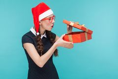Cunning businesswoman looking at gift box and want too open. Blue background. Studio shot Royalty Free Stock Photo