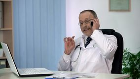 Cunning corrupt doctor hinting at bribe in phone conversation with patient royalty free stock images