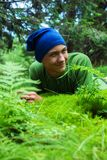 Cunning leprechaun, teenage boy with protruding ears. Is lying on a green meadow and smiling Royalty Free Stock Photos
