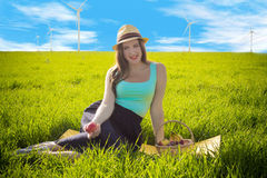 Cunning look of a beautiful woman in a dress against the background of wind generators royalty free stock image