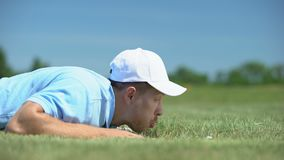 Cunning male golf player blowing ball in hole at course, successful shot, fun stock video