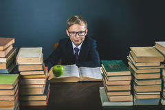 Cunning school boy sitting at the table with many book. S and one green apple. Smiling child dressed in school uniform and glasses. Blackboard. Student. Concept Royalty Free Stock Images